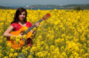 девушка на желтом поле с гитарой