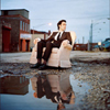 andrew bird in a chair in a puddle